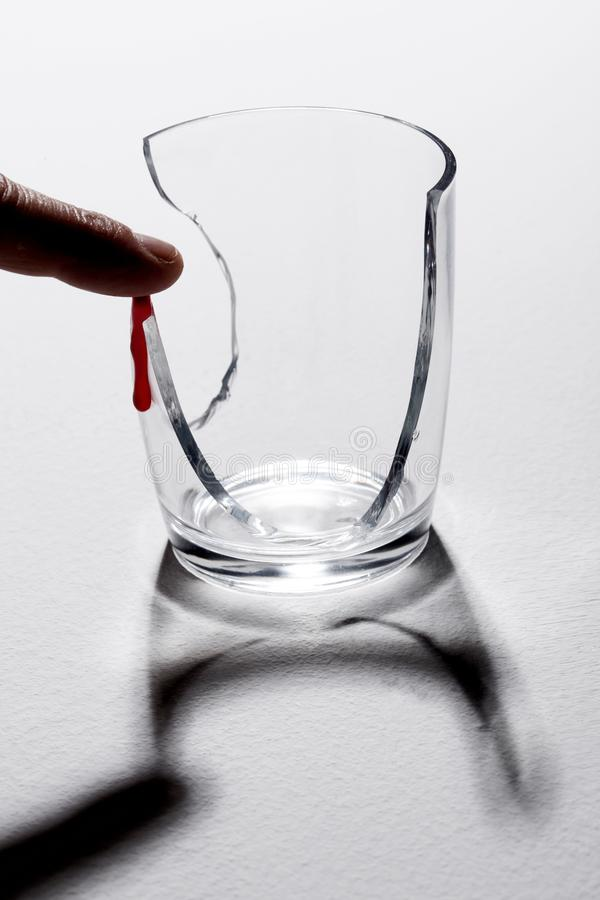 Doigt blessé sur un verre cassé et une baisse de la déchirure de sang photo libre de droits