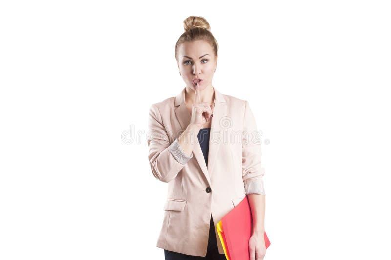 Doigt de femme d'affaires près de geste de lèvres d'isolement image stock