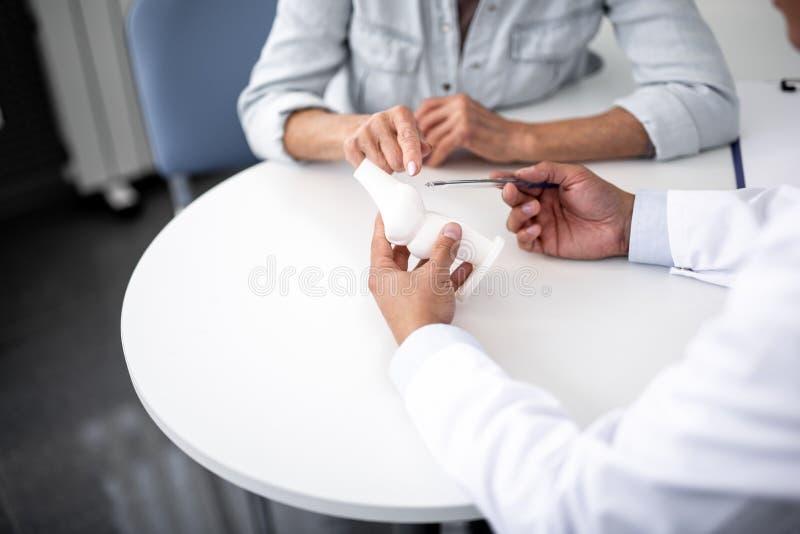 Doigt de femme indiquant le modèle de genou à disposition du docteur photo libre de droits