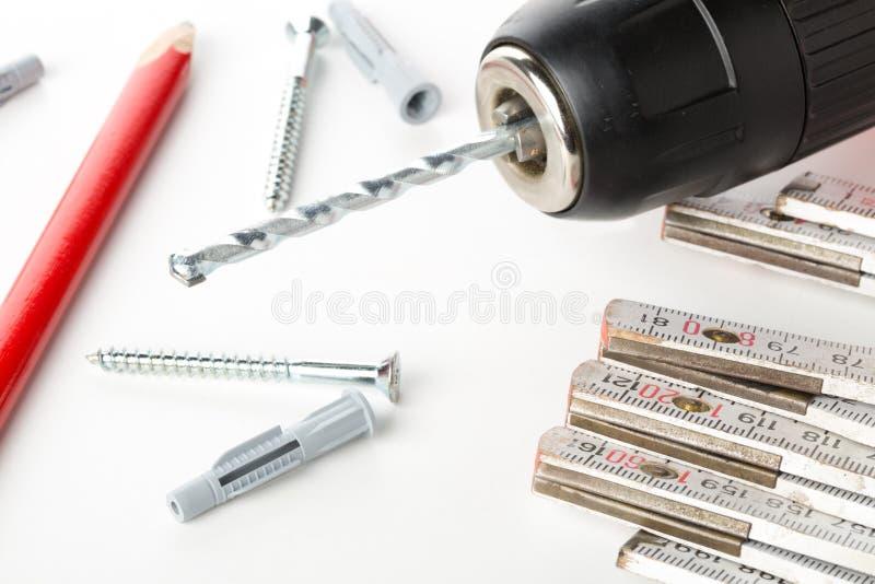 Doigt de prise de mur avec la vis, la perceuse de courant électrique, la règle de pliage et le crayon sur la table blanche photos stock