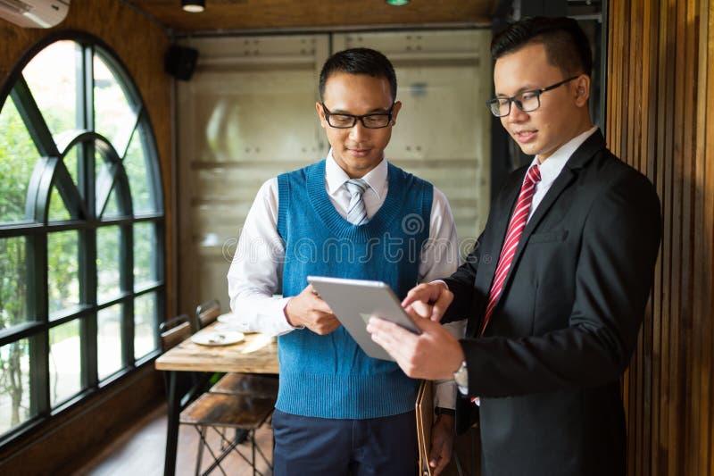 Doigt de regard et de point d'homme d'affaires de deux Asiatiques pour détailler dans le carnet, ils sont rencontrants et parlant image libre de droits