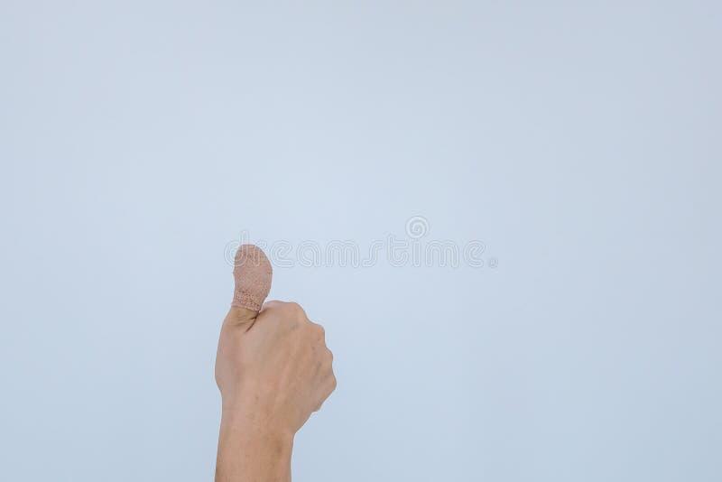Doigt douloureux blessé avec le bandage blanc La main a été blessée par l'accident et de représentation pouce  photographie stock