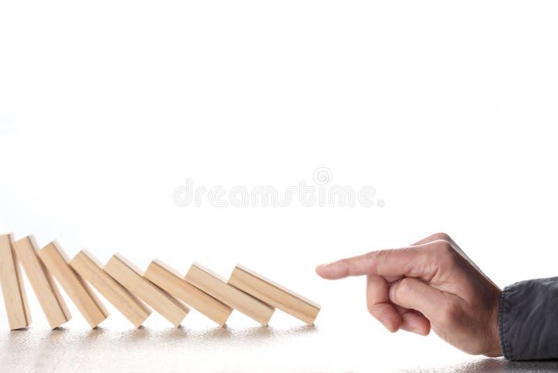 Doigt masculin poussant des blocs de domino avec l'isolat en baisse de réaction en chaîne sur le fond blanc avec l'espace de co image libre de droits