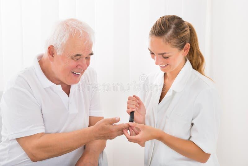 Doigt patient du ` s de docteur Using Lancelet On photo stock