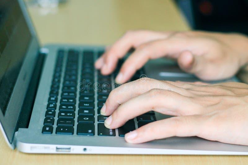 Doigts dactylographiant sur des clés d'ordinateur portable, vue de côté de plan rapproché photographie stock libre de droits