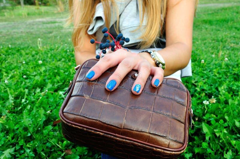 Doigts de femme avec la manucure bleue sur l'embrayage avec l'herbe verte image stock