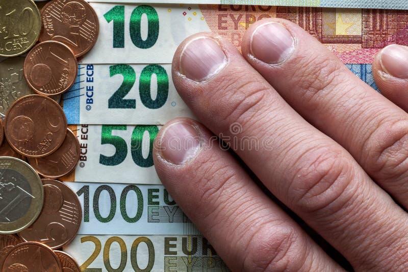 Doigts de main sur le fond de la pile d'une manière ordonnée disposée d'euro billets de banque, factures de devise en valeur l'eu photographie stock libre de droits