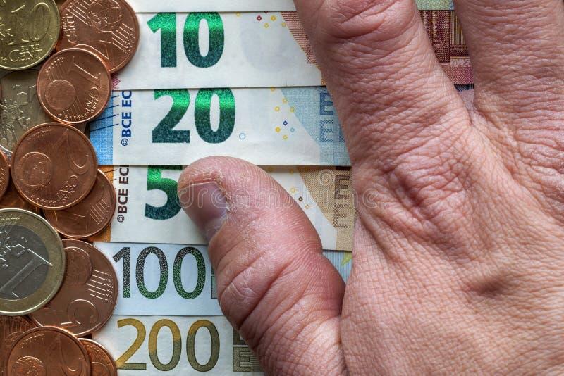 Doigts de main sur le fond de la pile d'une manière ordonnée disposée d'euro billets de banque, factures de devise en valeur l'eu image libre de droits