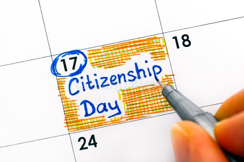 Doigts de personne avec le jour de citoyenneté de rappel d'écriture de stylo dans le cale photo stock