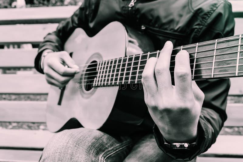 Doigts en gros plan du ` s de touche et de musicien de guitare là-dessus photographie stock