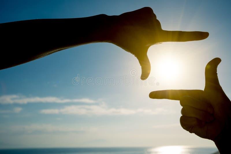 Doigts faisant des gestes le cadre de tableau photo stock