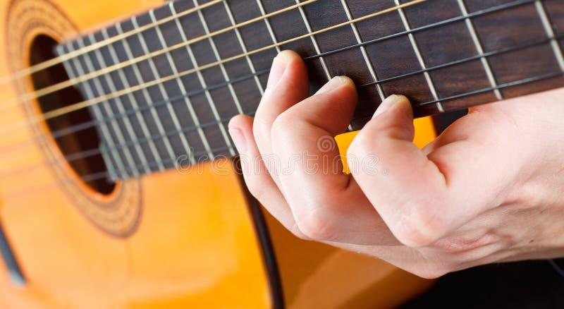 Doigts mâles jouant la guitare photos stock