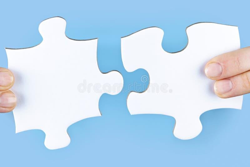 Doigts retenant des parties de puzzle denteux photos stock