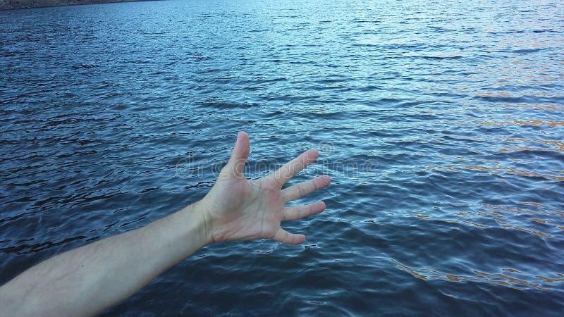 Doigts sur la mer image stock