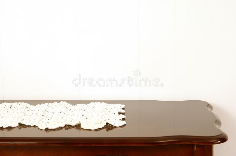 Doily on Table. Antique crocheted doily on polished cherry wood table royalty free stock image