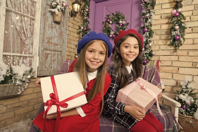 Doing Christmas gifts. Happy little girls hold gift boxes. Festive preparation for Christmas and New Year at home. Cute stock photos