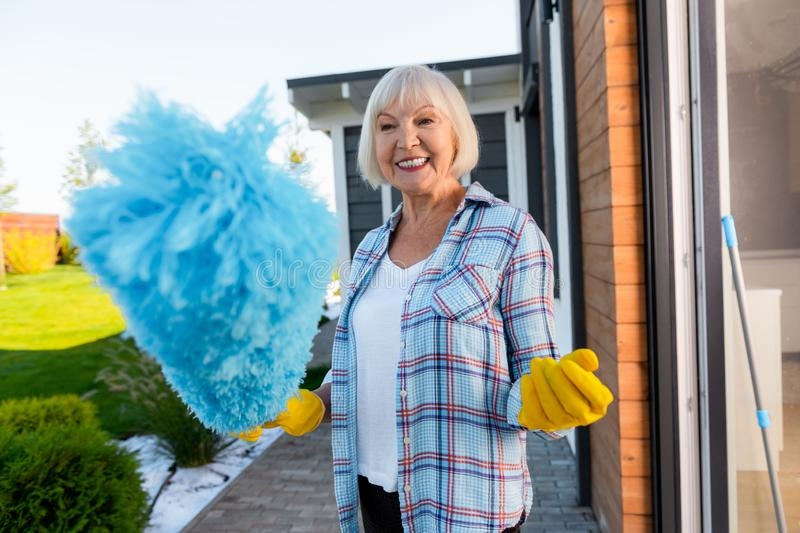 Beaming blonde-haired elderly lady doing cleaning near summer house stock photo