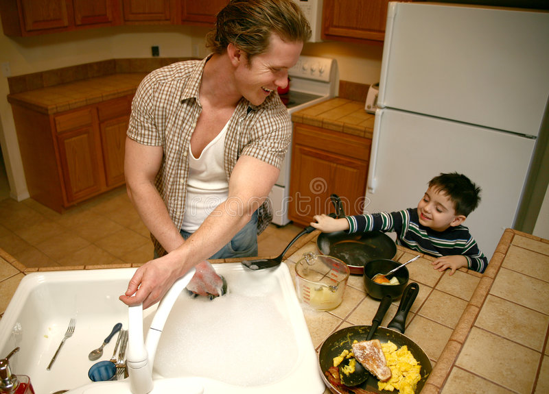 Doing Dishes. Toddler boy helping dad do the dishes. Focus on man smiling