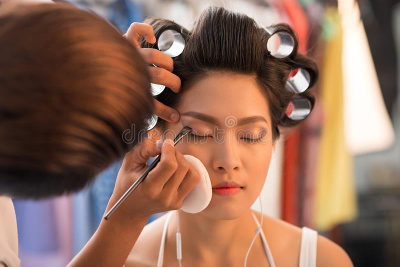 Doing evening make-up. Man doing professional make-up for young Vietnamese woman royalty free stock images
