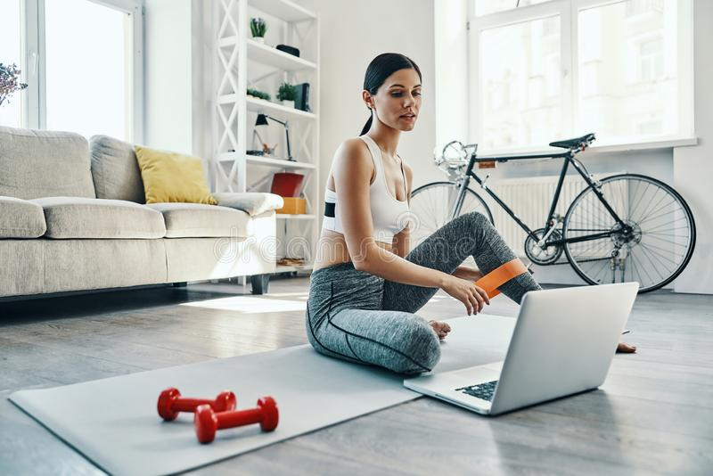 Doing everything right. Beautiful young woman in sports clothing using laptop while exercising at home royalty free stock photography