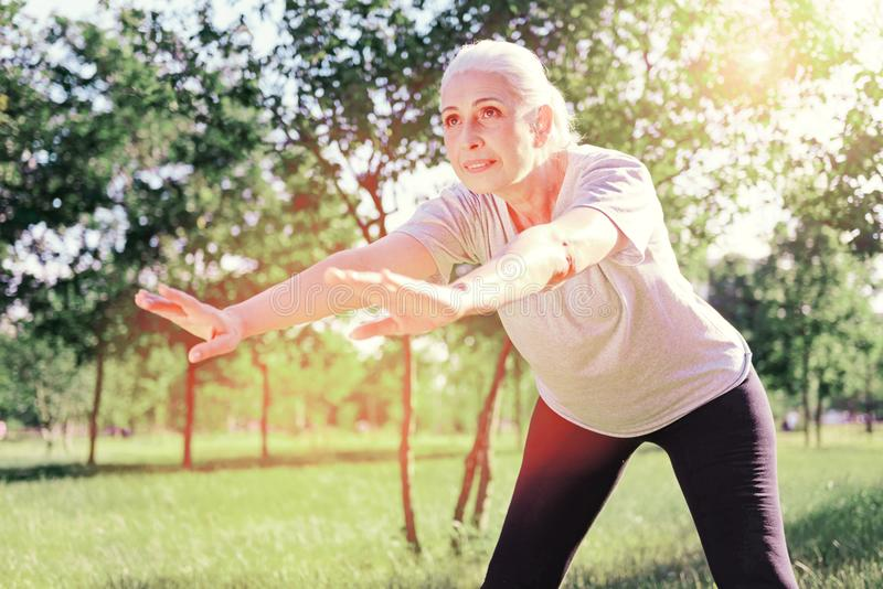 Concentrated elderly woman bending forward stock images