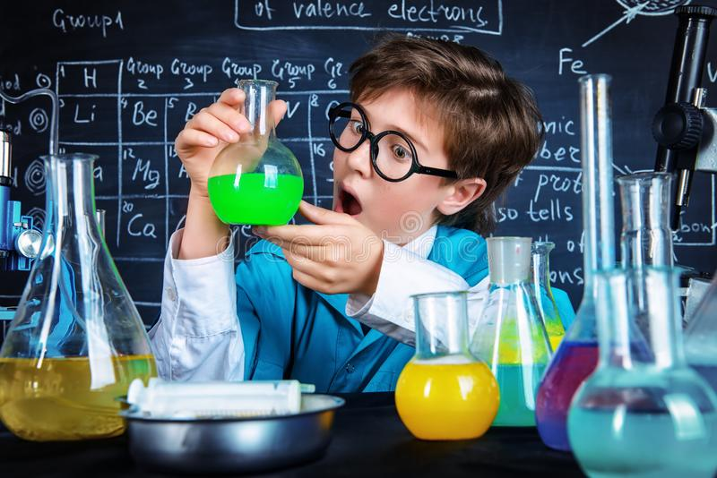 Doing experiments in a lab. Smart boy scientist making chemical experiments in the laboratory. Educational concept. Discovery stock photography