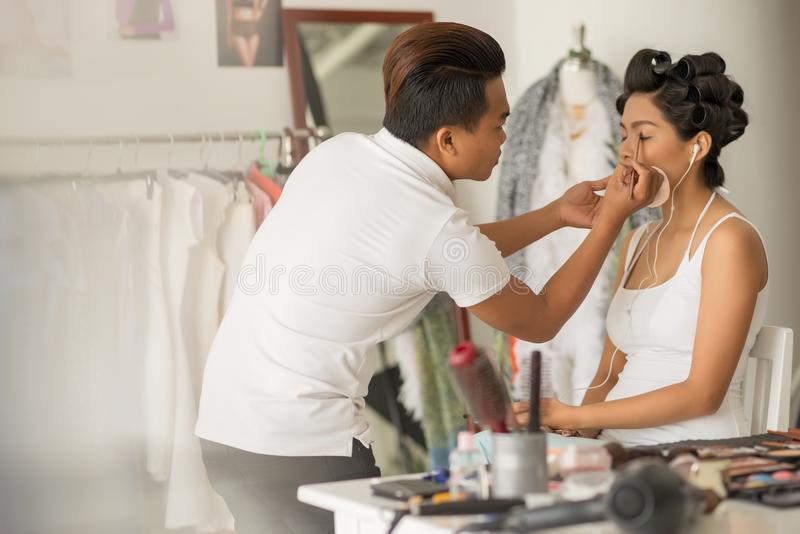 Doing eye make-up. Professional ma-up artist applying eyeshadows to enhance beauty of you woman royalty free stock images