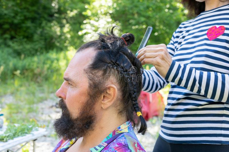 Doing haircut for men with long black hair. girl braids a pigtail to a middle-aged bearded man. Doing a haircut for man with long black hair. girl braids a royalty free stock photos