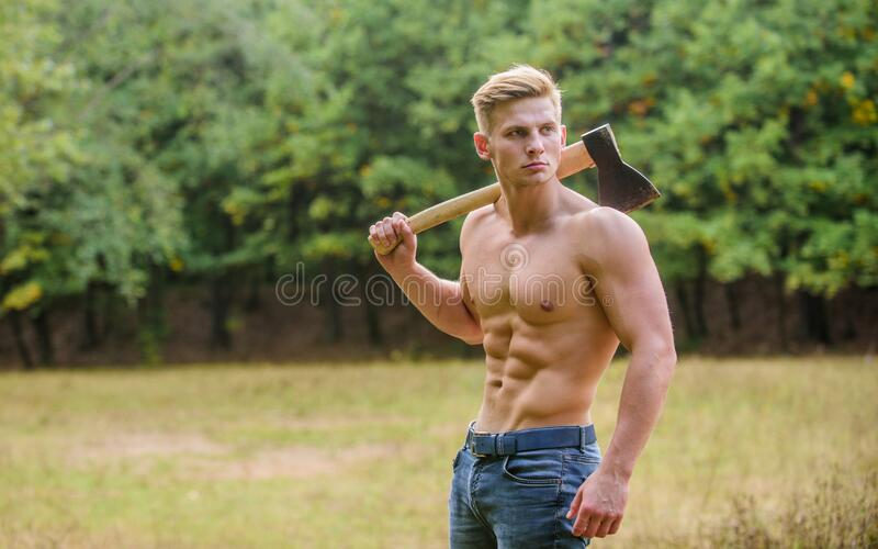 Doing his best. man strong body. muscular man with axe. sexy macho bare torso ax. brutal and attractive male in wood. Bodybuilder show his muscles. power and royalty free stock image