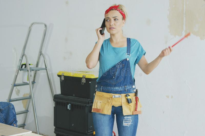 Doing home repairs woman talking on smartphone. Worried attractive young female in jeans overalls standing at white unpainted wall with instruments and talking royalty free stock image