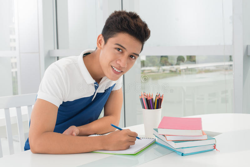 Doing homework. Portrait of a handsome student doing his homework royalty free stock image