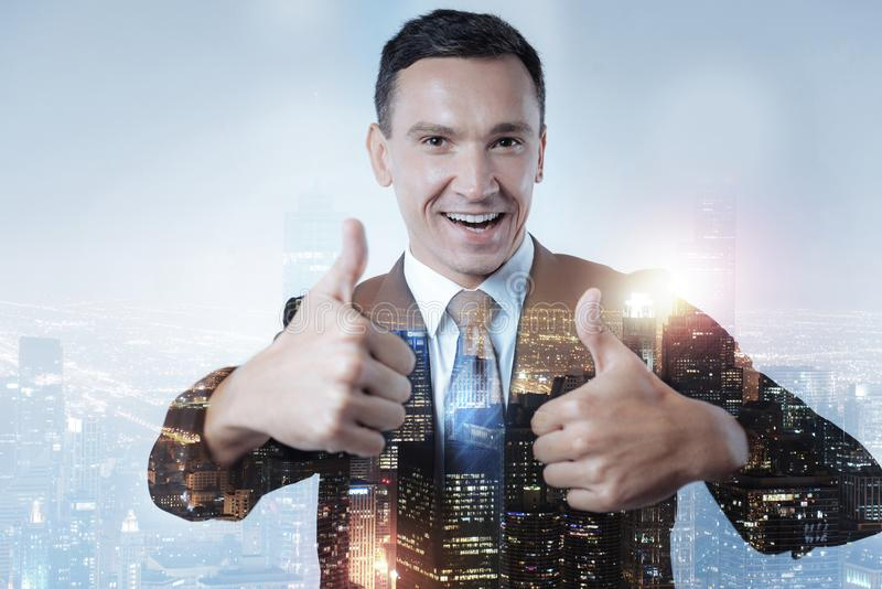 Optimistic manager raising two thumbs up stock photography