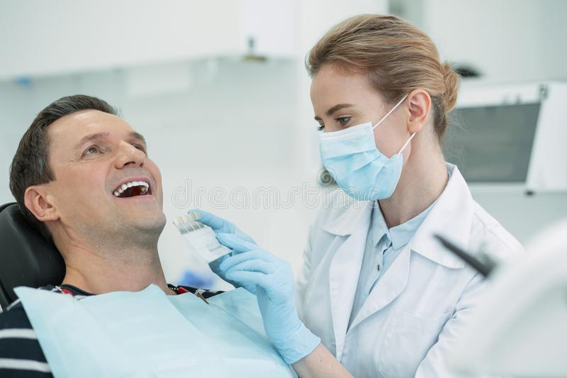Alert doctor taking care of her patients teeth stock photography