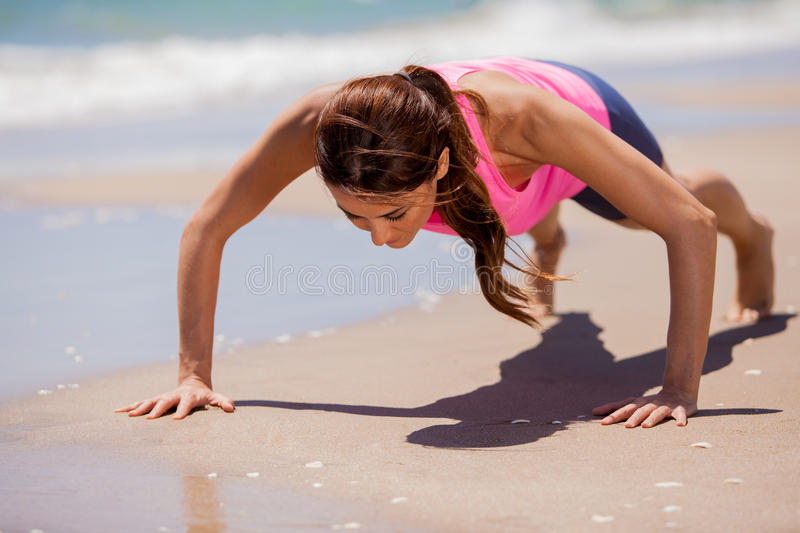 Doing push-ups at the beach. Young athletic brunette training and doing some push-ups at the beach stock photography