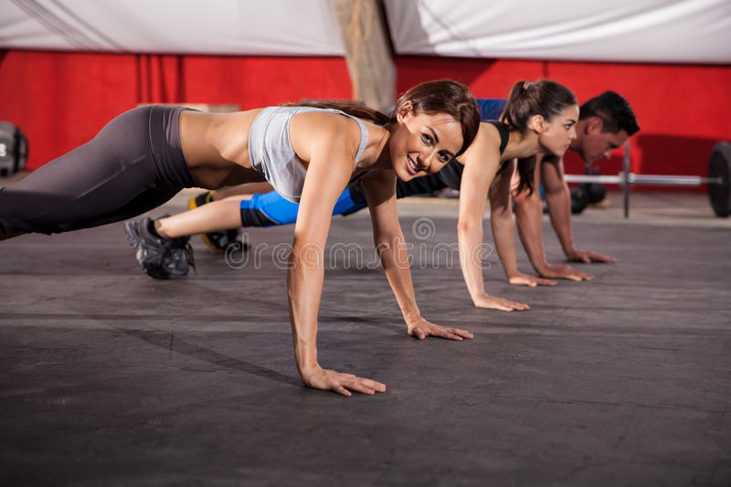 Doing push ups at a gym. Three athletic Hispanic people doing some push ups at a cross-training gym royalty free stock photos