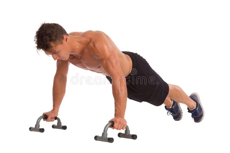 Doing Push Ups With Handles. Muscular man doing a push ups with handles. Full length studio shot isolated on white stock photography