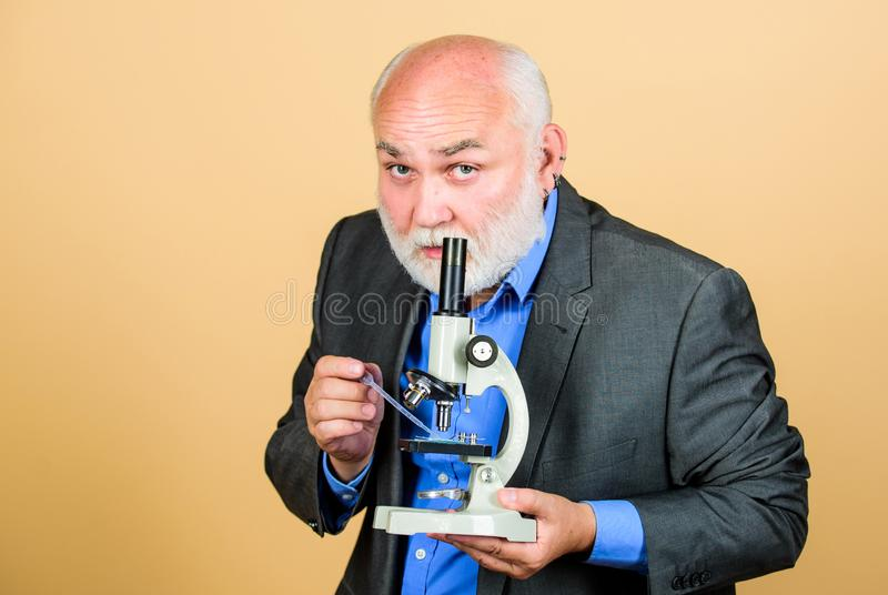 Doing research. chemistry in school laboratory. mature bearded teacher with microscope. senior man biologist. university stock images