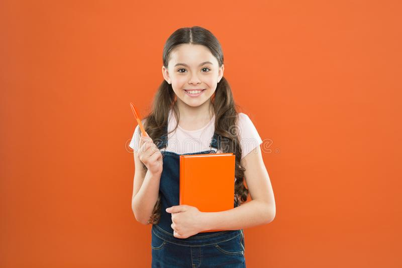 Doing research. literature lesson. back to school. happy little girl with notebook. school girl read book on orange. Background. writing notes. kid diary royalty free stock photos