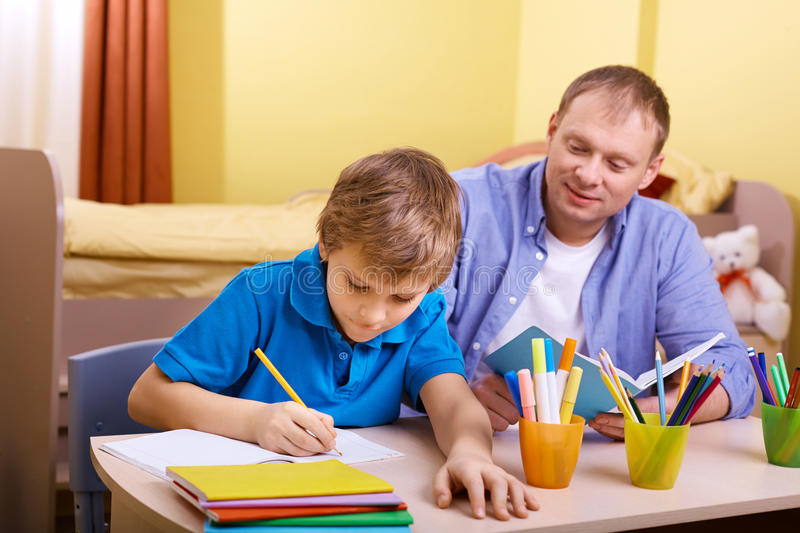 Doing schoolwork. Portrait of cute schoolboy and his father making schoolwork at home stock photography
