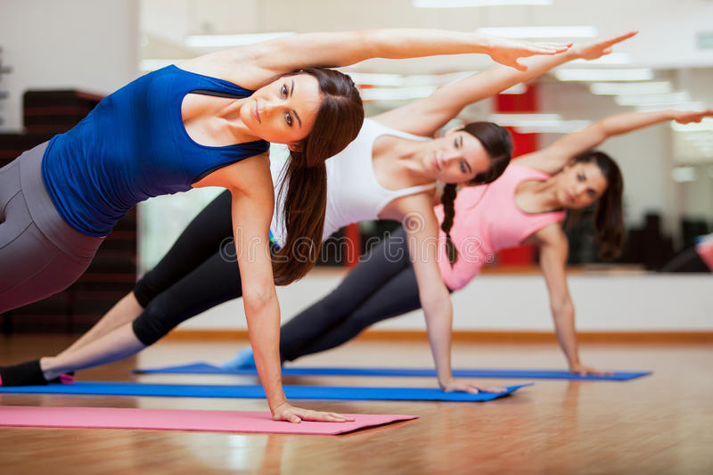 Doing a side plank for yoga class. Beautiful group of women practicing the side plank yoga pose during a class in a gym stock image
