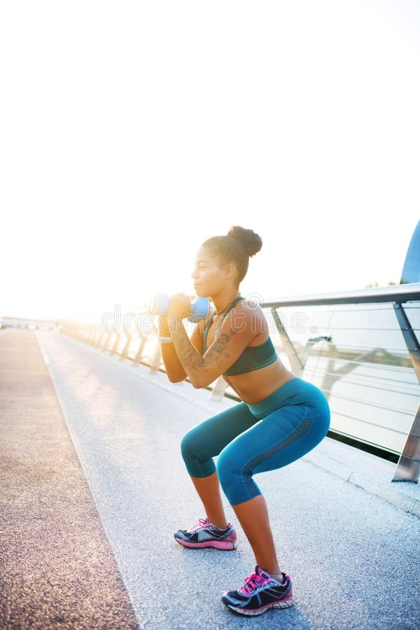 Dark-skinned woman doing sit ups with dumbbells. Doing sit ups. Dark-skinned woman wearing short top doing sit ups with dumbbells stock image