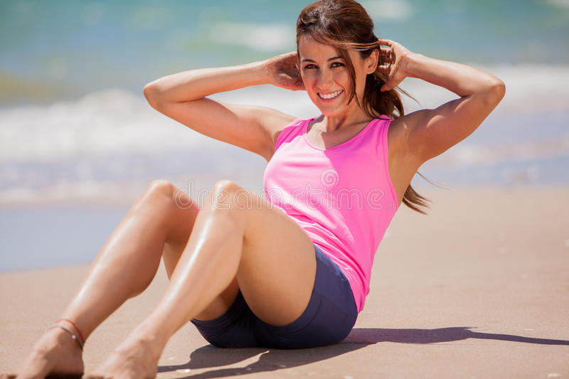 Doing some abs at the beach. Cute young brunette doing some abs at the beach and smiling royalty free stock image