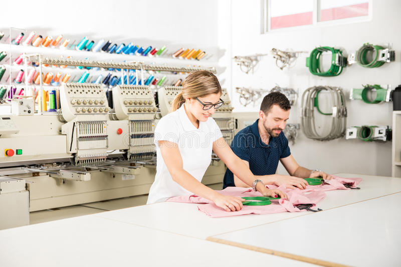 Doing some embroidery in a workshop. Wide view of two people getting some garments ready for embroidery in a textile factory royalty free stock photos
