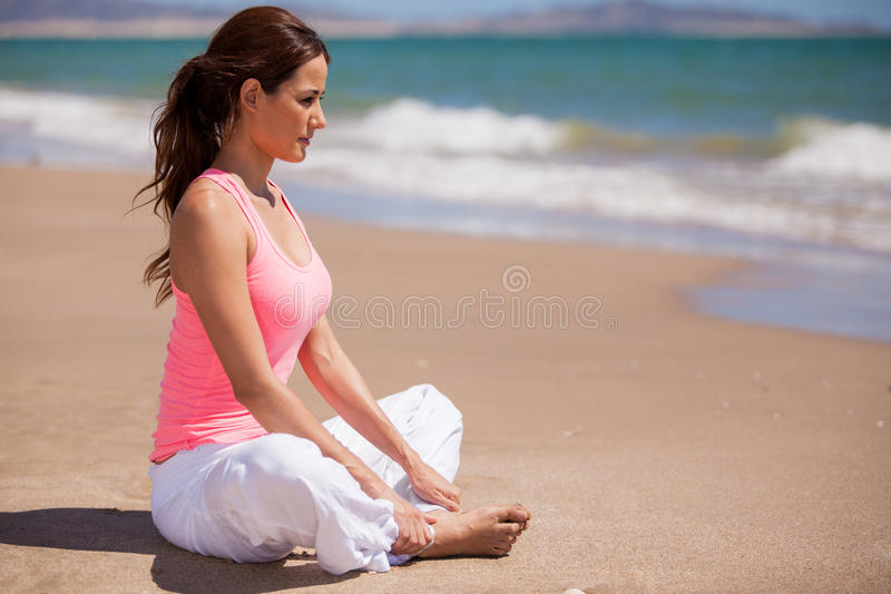 Doing some meditation at the beach. Beautiful young woman sitting at the beach and meditating royalty free stock photo