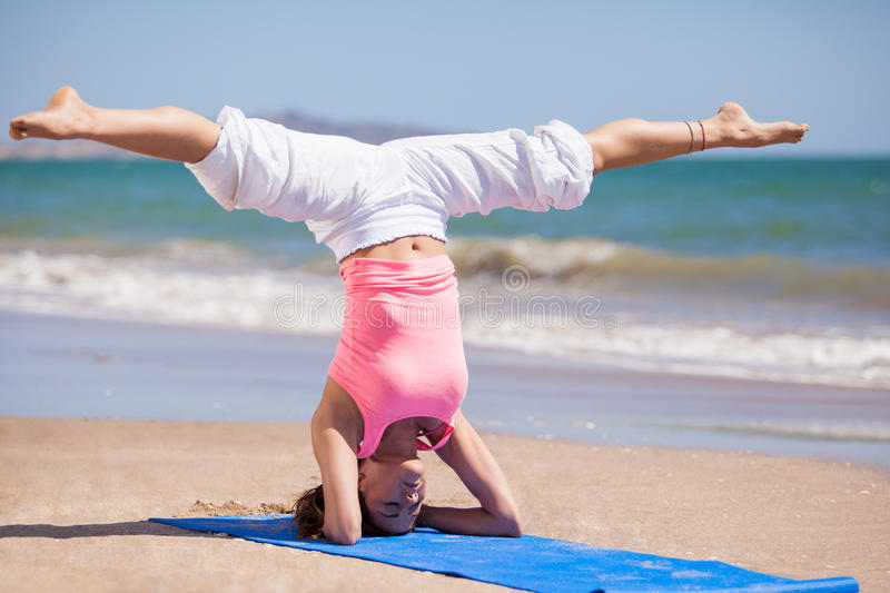 Doing some yoga at the beach. Beautiful young woman standing on her head with her legs spread as part of a yoga pose at the beach royalty free stock images