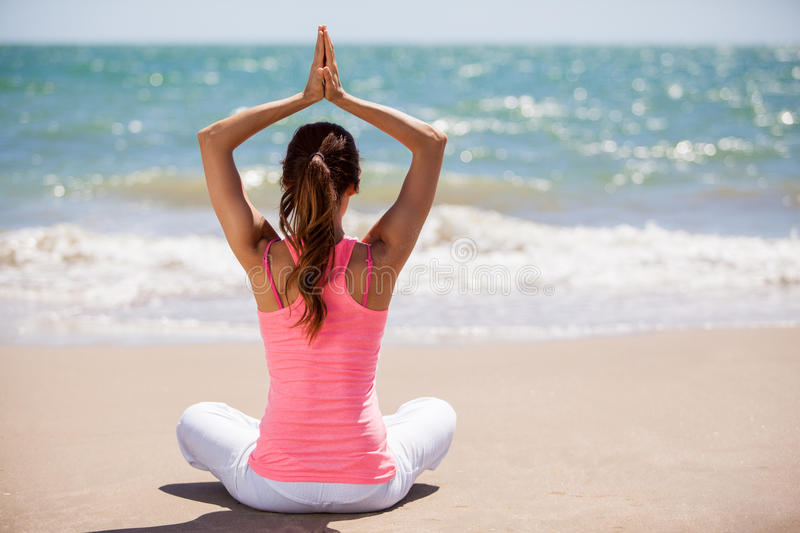Doing some yoga on a sunny day. Young woman meditating and practicing some yoga at the beach stock images