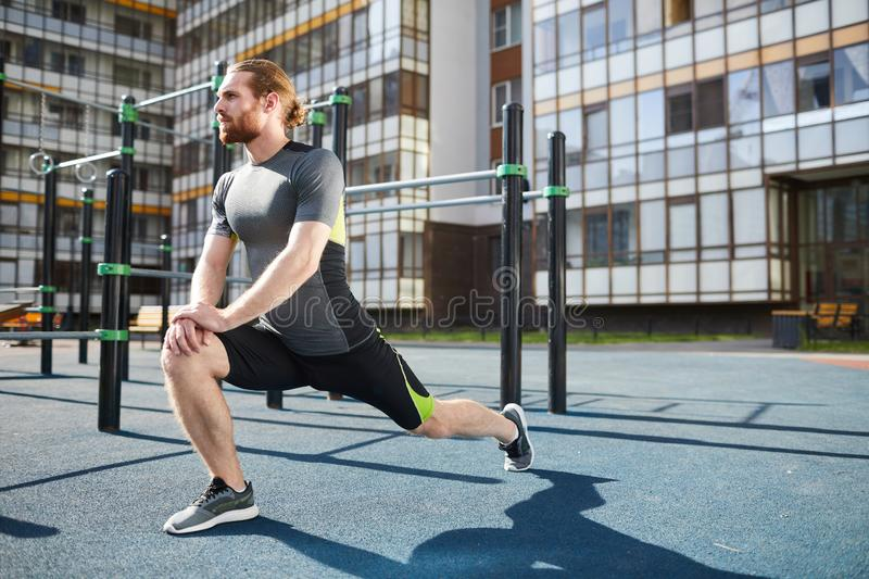 Doing static stretching of legs stock images