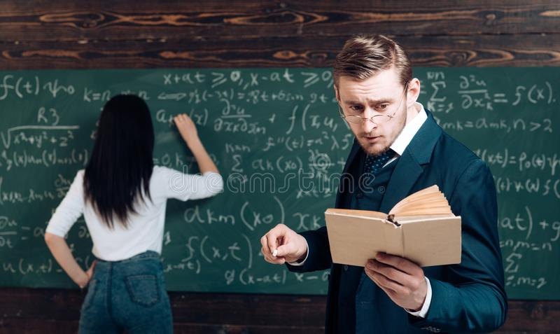 Doing sums. Rear view woman write equation on chalkboard. Learning math enables me to think clearly. Teacher man in royalty free stock photos