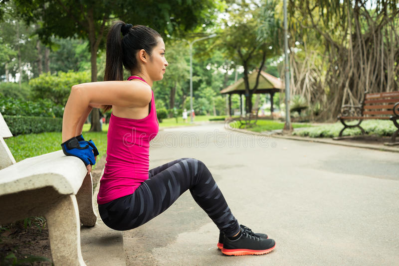 Doing triceps bench dips. Young woman doing triceps bench dips in the park, side view stock images