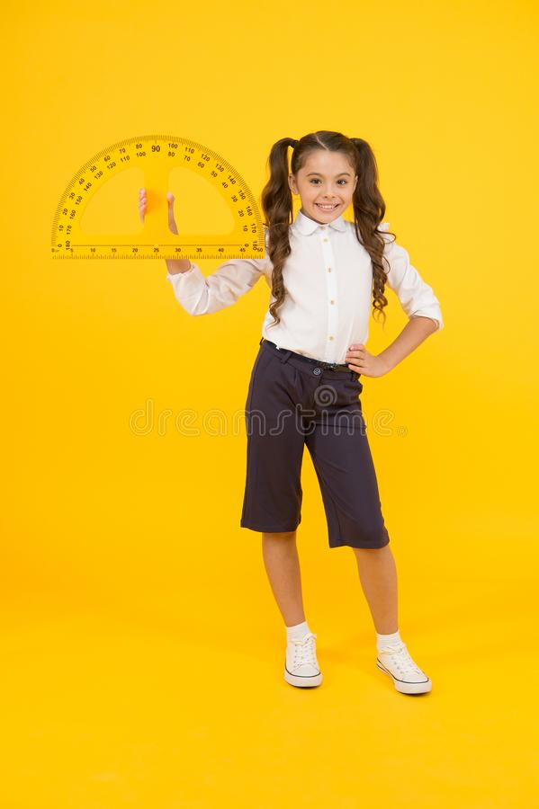 Doing well at maths. Cute little schoolgirl holding measuring tool for maths on yellow background. Small child with royalty free stock image